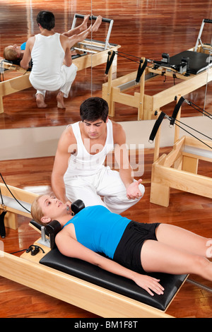 Male instructor assisting a woman in a gym - Stock Photo