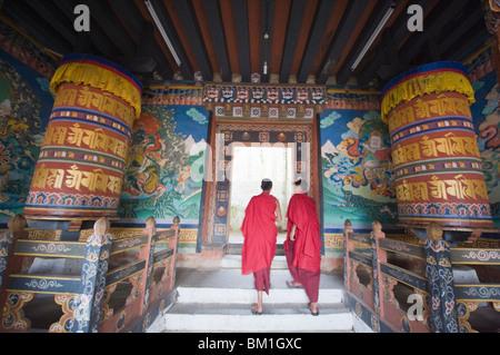 Monks walking between prayer wheels at Trongsa Dzong (Chokhor Raptentse) dating from 1648, Bhutan Asia - Stock Photo