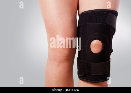 Knee brace on a person's knee - Stock Photo