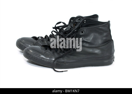 two old worn black leather high top basketball shoes on white - Stock Photo