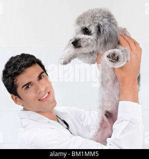 Vet carrying a dog - Stock Photo
