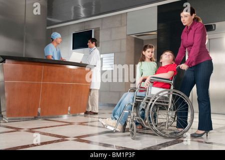 Woman pushing her son in a wheelchair - Stock Photo