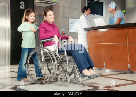 Girl pushing her mother in a wheelchair - Stock Photo