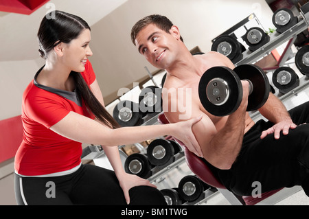 Woman touching a man's bicep as he exercising with a dumbbell - Stock Photo