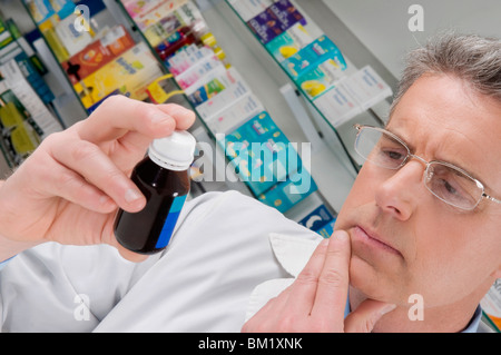 Pharmacist holding a medicine bottle and thinking - Stock Photo