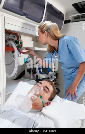 Female nurse assisting a patient in an ambulance - Stock Photo