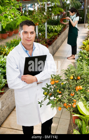 Scientist holding a clipboard in a greenhouse - Stock Photo