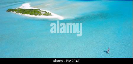 Catamaran sailing near a desert island, the Maldives, Indian Ocean - Stock Photo