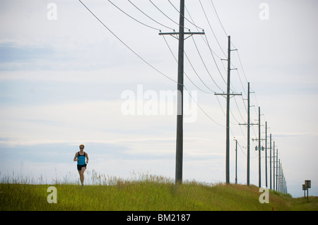 Woman running beneath power lines, Bozeman, Gallatin County, Montana, USA - Stock Photo