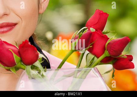 Woman smelling flowers in a greenhouse - Stock Photo