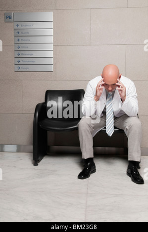 Doctor sitting on a chair and looking stressed - Stock Photo