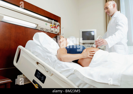 Pregnant woman going through an ultrasound scan - Stock Photo