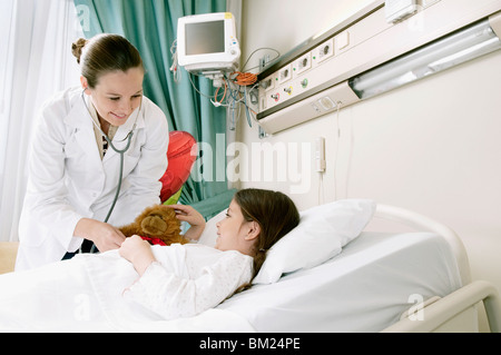 Girl on a hospital bed being examined by a female doctor - Stock Photo
