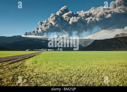 Ash cloud from the Eyjafjallajokull eruption in Iceland towering over a nearby farm - Stock Photo