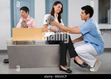 Pets with their owners in a veterinary hospital - Stock Photo