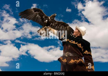 Eagle hunter with his golden eagle (Aquila chrysaetos) on his arm, Issyk Kol, Kyrgyzstan, Central Asia
