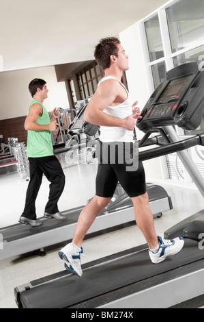 Two men running on treadmills - Stock Photo