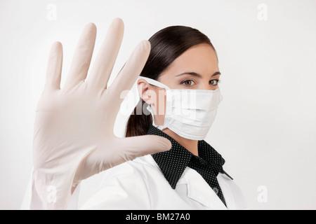 Female doctor wearing a flu mask - Stock Photo