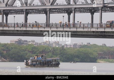 Passenger ferry under Howrah Bridge, Kolkata, West Bengal, India, Asia - Stock Photo