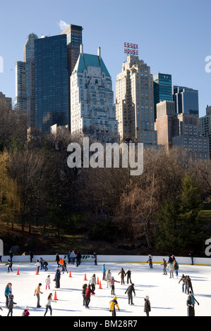 Skaters on the Woolman Rink in Central Park with the skyline behind, New York City, New York State, USA - Stock Photo