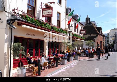 Diners eat alfresco style outside at the Donatello Italian restaurant in Brighton city centre UK - Stock Photo