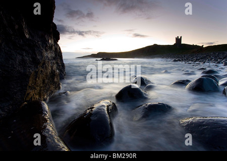 View across the Rumble Churn at dawn towards the ruins of Dunstanburgh Castle, Embleton Bay, Northumberland, UK - Stock Photo