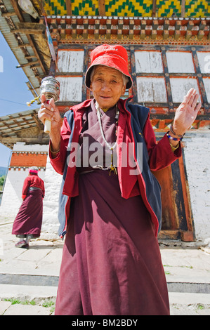 Woman spinning a prayer wheel, Jampay Lhakhang, built in 659 by Tibetan King Songtsen Gampo, Jakar, Bumthang, Bhutan - Stock Photo