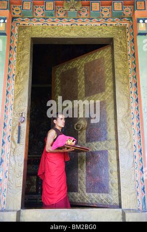 Young monk at a temple doorway, Khamsum Yuelley Namgyal Chorten built in 1999, Punakha, Bhutan - Stock Photo