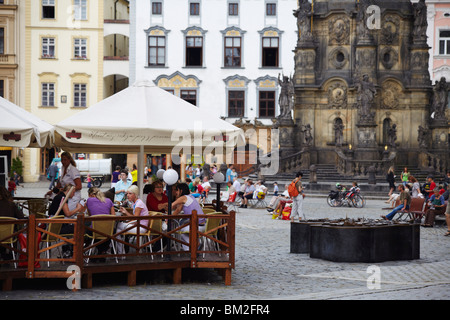 Outdoor cafe in Upper Square with Holy Trinity Column, UNESCO World Heritage Site, Czech Republic - Stock Photo