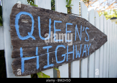 A rustic wooden sign pointing the way to Queen's Highway in Hope Town on Elbow Cay in the Abacos, Bahamas. - Stock Photo
