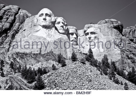 Three people on top of the carvings at Mount Rushmore to show scale, Keystone, South Dakota, United States. - Stock Photo