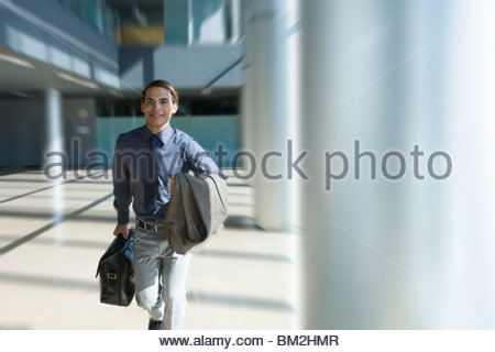 Businessman rushing through office lobby - Stock Photo