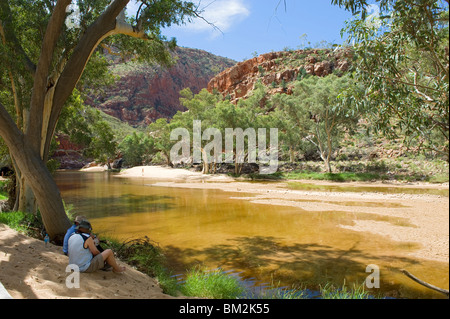 Two people sitting in the shade of trees overlooking the waterhole at Ormiston Gorge in the Western MacDonnell Ranges - Stock Photo