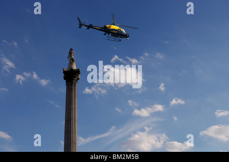 Nelsons Column and police helicopter, London, UK - Stock Photo