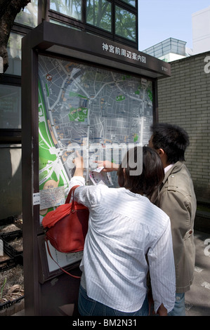 Visitors looking at a Tokyo city map in the Omotesando neighbourhood of Shibuya, Tokyo, Japan - Stock Photo