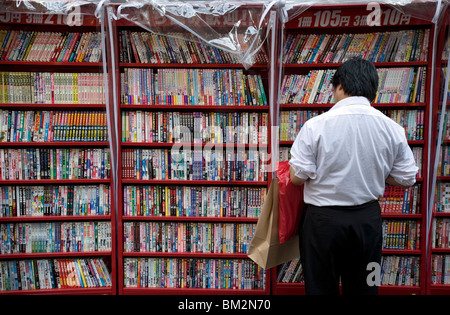 Man browsing Japanese manga comic books at a shop in Osaka, Japan - Stock Photo