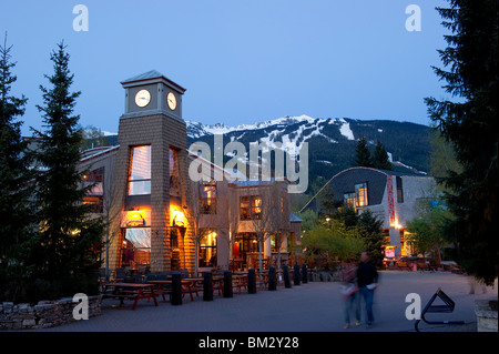 Whistler Village at Dusk with the Brew Pub restaurant and clock tower with Blackcomb mountain in the background - Stock Photo