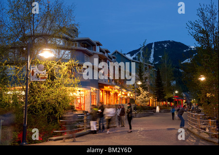 Village Stroll in Whistler Village at Dusk with Whistler Mountain in the distance - Stock Photo