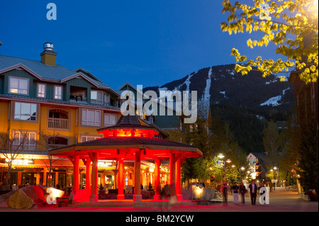 Town Plaza in Whistler Village at Dusk with Whistler Mountain in the background - Stock Photo