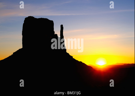 Monument Valley dawn - sun rises behind west mitten - Arizona and Utah, USA - Stock Photo