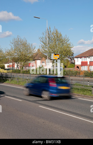 A blue car speeding past a Gatso speed camera on the A316 Great Chertsey Road, Hounslow, UK. SEE DESCRIPTION - Stock Photo