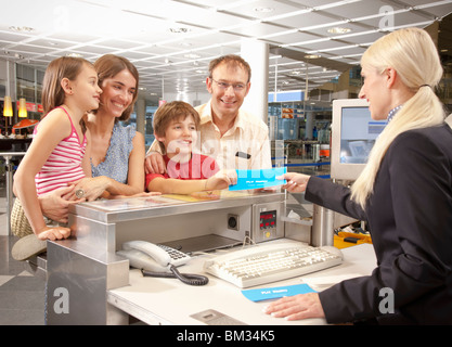 Family checking at the airport desk - Stock Photo