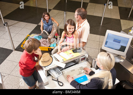 Mother checkin suitcase for vouchers - Stock Photo