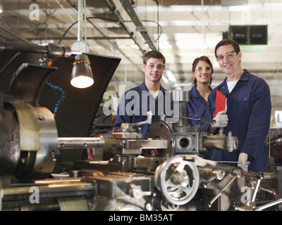Engineer With Male & Female Apprentices - Stock Photo