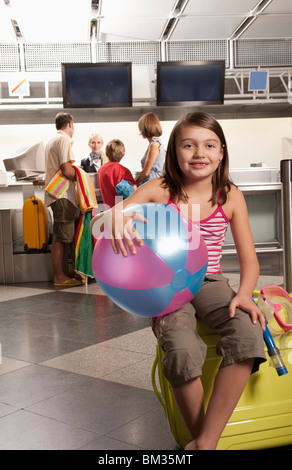 Little girl sitting on a suitcase - Stock Photo