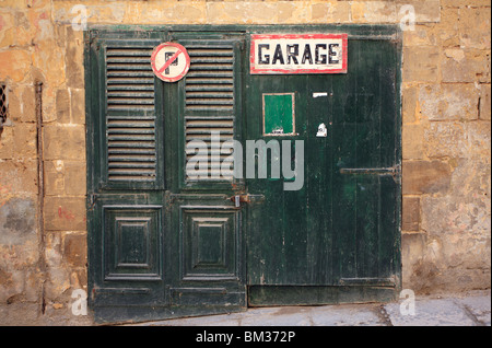 A garage doorss in a 'French' style with horizontal slats, a 'no parking' sign, a 'garage sign' green and aged, - Stock Photo