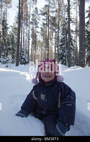 Baby toddler plays play path track through snow covered forest near Godby on land Aland archipelago Finland Winter - Stock Photo