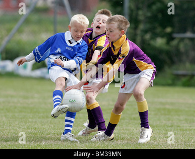 action from the belfast junior gaa schoolboys irish football tournament young boys playing gaelic football - Stock Photo