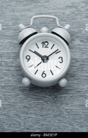 small cute alarm clock monochrome photograph on the wooden table - Stock Photo