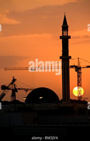 Qatar, Doha, Grand Mosque minaret with construction cranes and setting sun - Stock Photo